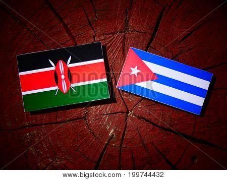 Kenyan Flag With Cuban Flag On A Tree Stump Isolated