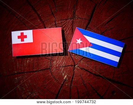 Tonga Flag With Cuban Flag On A Tree Stump Isolated