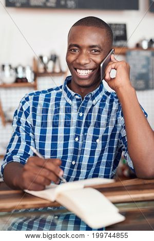 Smiling young African entrepreneur talking on a cellphone and writing in a notebook while standing at the counter of his cafe