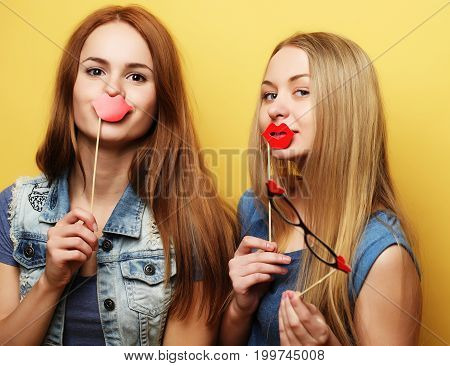 Happy time. Stylish sexy hipster girls best friends ready for party. Over yellow background.