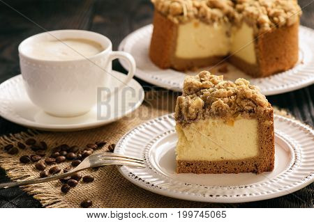 Homemade cheesecake with capuccino on wooden table.