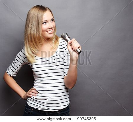 Happy singing girl. Beauty woman wearing  t-shirt   with microphone over grey background.
