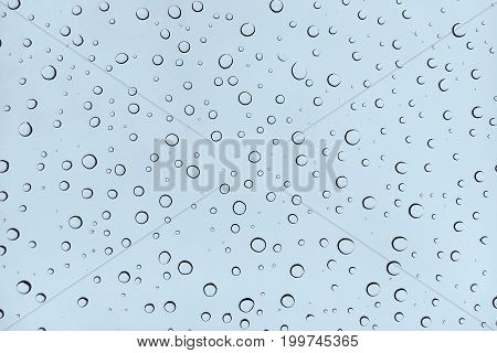 Close up water drops on glass blue background