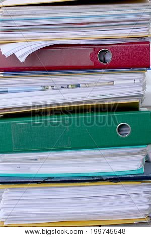 Pile of different file folders or ring binders full with office documents and paper work