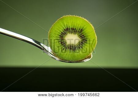 Sliced fresh and juicy green kiwi fruit on spoon with green light background for healthy food and fruit salad concept