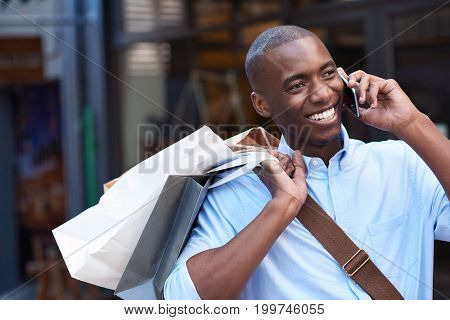 Stylish young African man smiling and talking on his cellphone while carrying paperbags while out shopping in the city
