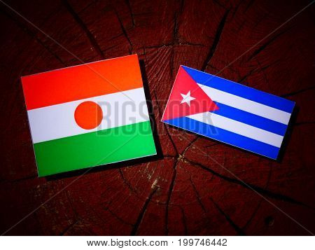 Niger Flag With Cuban Flag On A Tree Stump Isolated