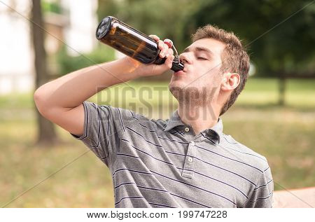 Young Man Drinking A Beer In The Park