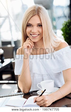 Creative personality. Happy delighted attractive woman holding a pencil and looking at you while writing in her notebook