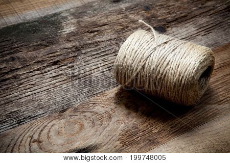 Rope jute coil on old wooden background