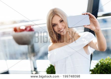 Modern device. Selective focus of a modern innovative smartphone being used for taking a selfie by a nice happy delighted woman