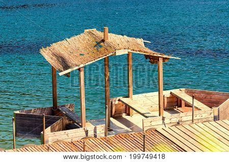 Boat bridge with simple boat house or wooden boat with thatched roof.