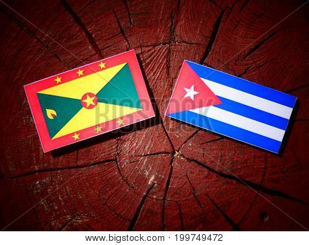 Grenada Flag With Cuban Flag On A Tree Stump Isolated