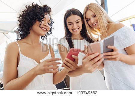 Digital natives. Happy positive young women standing together and holding their smartphones while exchanging the information