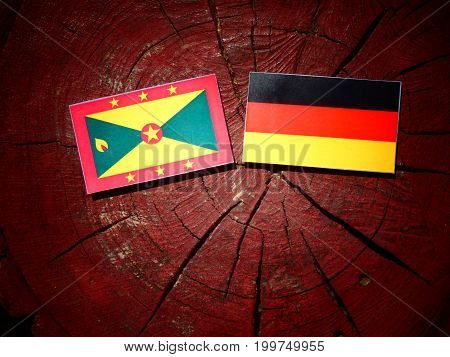 Grenada Flag With German Flag On A Tree Stump Isolated