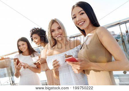 Pleasurable time. Happy joyful female friends smiling and having a great time while meeting together