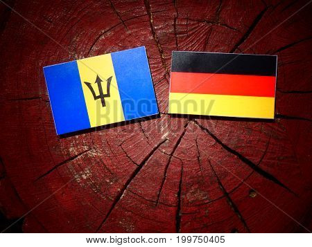 Barbados Flag With German Flag On A Tree Stump Isolated