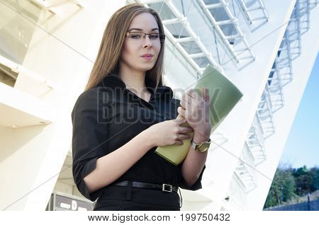 Attractive businesswoman dressed in black and wearing glasses holding a yellow folder with papers. Cunningly smiling looking at the camera. Horizontal photo