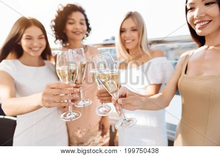 Sparkling wine. Selective focus of four glasses being filled with champagne while being held by a cheerful beautiful good looking women