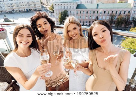 Young and beautiful. Attractive pleasant delighted women holding glasses with champagne and smiling while sending you a kiss
