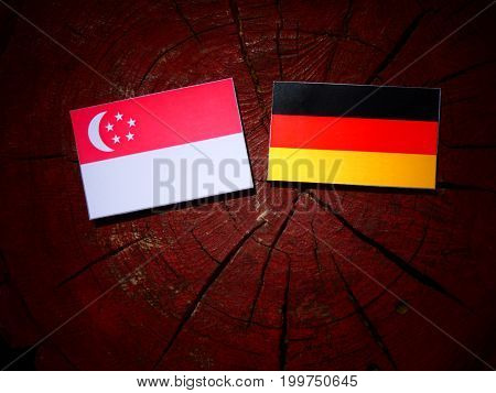 Singaporean Flag With German Flag On A Tree Stump Isolated