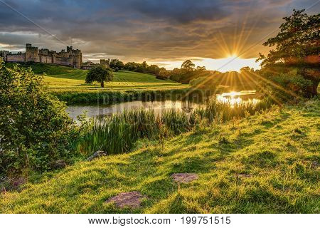 Sunbeams over River Aln at Alnwick, which runs through Northumberland from Alnham to Alnmouth. Seen here below Alnwick Town and Castle on the skyline as the sun goes down