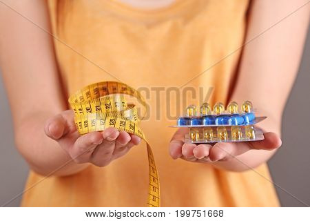 Young woman holding packs of pills and measuring tape in hands, closeup. Weight loss concept