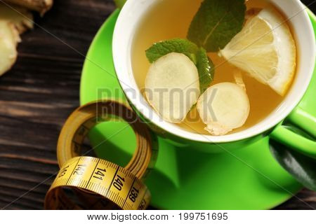 Cup of tea with ginger, mint, lemon and measuring tape on table, closeup. Weight loss concept