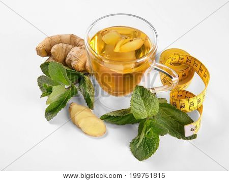 Composition with cup of tea, ginger, mint leaves and measuring tape on white background. Weight loss concept