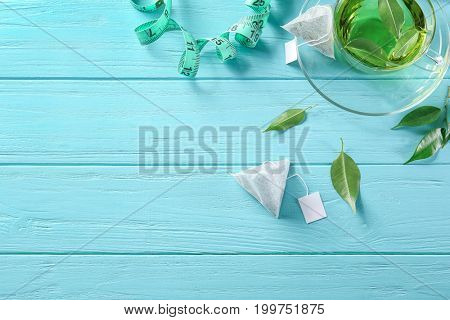 Composition with teabags, measuring tape and cup on wooden table. Weight loss concept