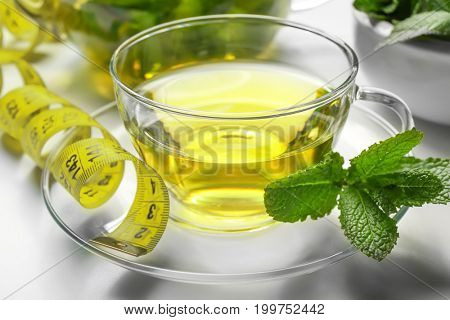 Closeup view of cup with tea, mint leaves and measuring tape on table. Weight loss concept