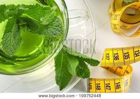 Cup of herbal tea and measuring tape on white background, closeup. Weight loss concept