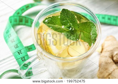 Cup of ginger tea with lemon, mint and measuring tape on table, closeup. Weight loss concept