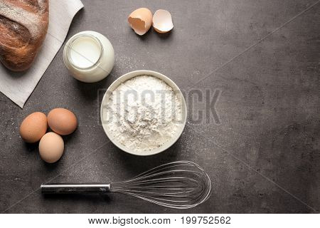 Bowl with white flour, eggs, bread, milk in jar and whisk on kitchen table