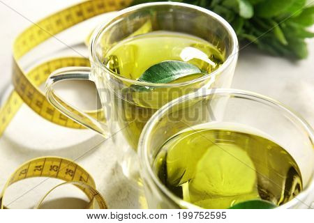 Cups of tea and measuring tape on table, closeup. Weight loss concept