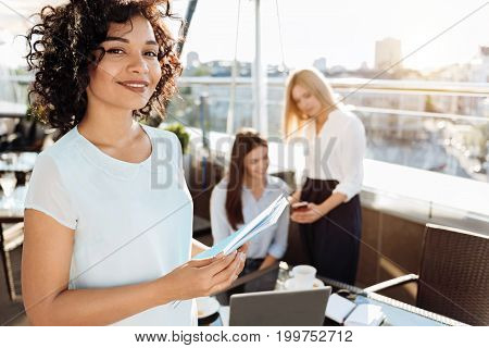 Our project. Joyful attractive pleasant woman holding documents and smiling while organizing a startup with her friends