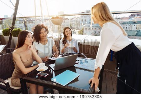 Working in team. Happy positive smart women sitting at the table and smiling while looking at their team leader
