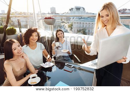 Showing a presentation. Delighted happy positive woman holding a laptop and pointing at it while showing a presentation to her colleagues