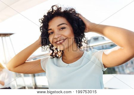 Charming woman. Positive delighted magnetic woman holding her hair and smiling while looking at you