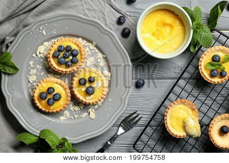 Delicious crispy tarts with blueberries and custard cream on table
