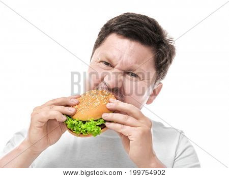 Overweight man eating burger on white background. Diet concept