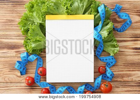 Blank notebook, healthy fresh food and measuring tape on wooden table. Weight loss concept