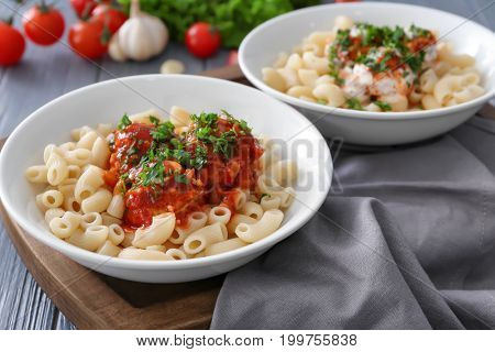 Bowls with delicious pasta and turkey meatballs on wooden board
