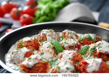 Frying pan with delicious turkey meatballs and sauce, closeup