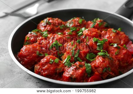 Frying pan with delicious turkey meatballs on table