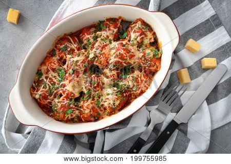 Ceramic casserole dish with turkey meatballs, tomato sauce and melted cheese on table