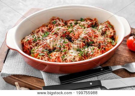 Ceramic casserole dish with turkey meatballs, tomato sauce and melted cheese on wooden board