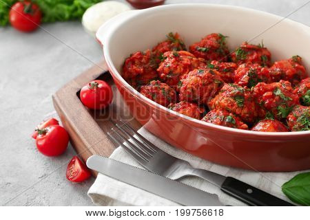 Ceramic casserole dish with turkey meatballs and tomato sauce on table