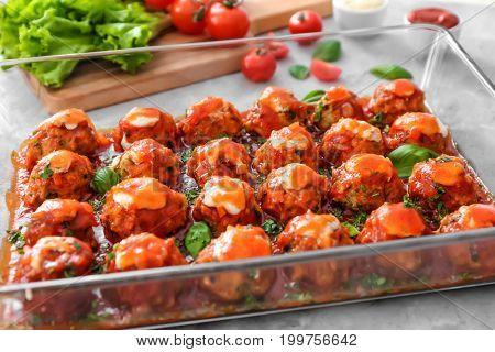 Delicious turkey meatballs in glass casserole dish on light table