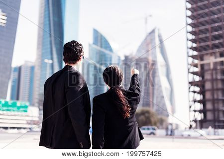 a businessman and businesswoman, or possibly architects, standing in the streets of dubai and pointing at a construction site in the background
